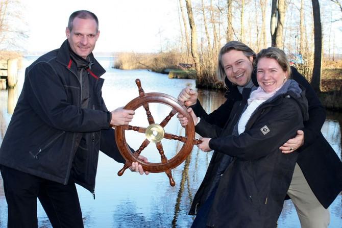 Michael Haufe übergibt symbolisch das Steuer an die beiden Geschäftsführer Isabel Lippold und Aaron Backhaus